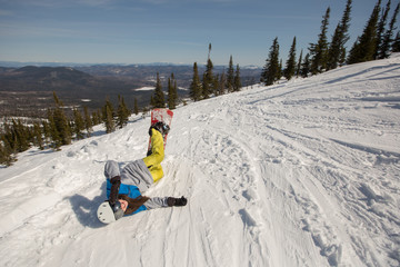 Happy Female snowboarder lying on the snow on mountain top. Winter sport, snowboard freeride