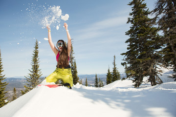 Young happy snowboarder female have fun and enjoy snow and winter in snow mountain forest