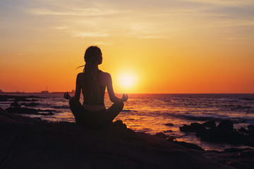 Silhouette young woman sitting in lotus pose, practicing yoga on ocean beach at sunset