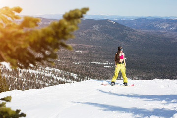 Portrait of young snowboarder woman standing on snowboard on mountain top. Sunny winter holiday, winter sport outdoor, free people