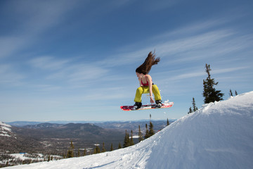 Portrait of happy young snowboarder female jumping on snowboard with waving hair. Sunny winter holiday, winter sport outdoor, free people