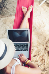 Female wearing hat and swimsuit sitting in hammock in tropical park outdoor using laptop computer. Fingers on keyboard