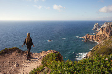 Woman staying on ocean cliff, tourist at westernmost point of Europe, Cabo da Roca, Portugal