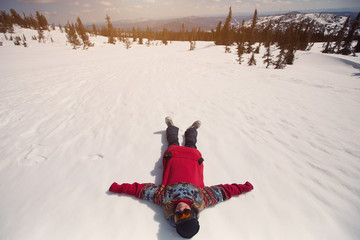 Snowboarder female lying on snow field mountains top. Winter sport holiday