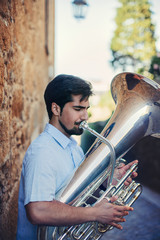 Close view portrait of  Street musician playing tuba outdoor in European city