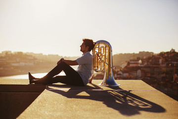 Street musician sitting with tuba outdoor at sunset. Europe city background