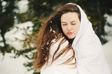 Portrait of young woman with long brown hair in white blanket in winter forest outdoor