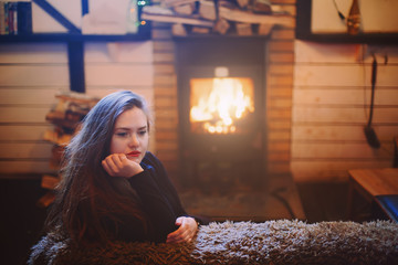 Portrait of young female sitting near fireplace