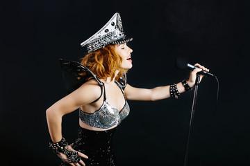 portrait of woman singer with microphone in dark studio background