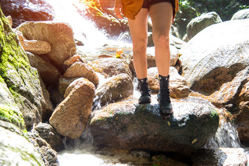 Close up leg hiker asian woman walk a way in the water fall, background forest.  Travel Concept