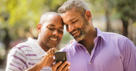 Happy Lgbt Gay Couple Looking At Pictures On Mobile Phone