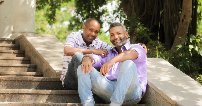 Portrait Of Two Gay Men Smiling At Camera In Park