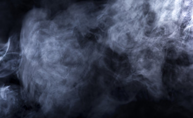 Smoke from a Vape with light effects on a black background.  Abstract texture with copy or text space.  It has patterns showing movement and depicts a spooky mood with a Halloween theme.