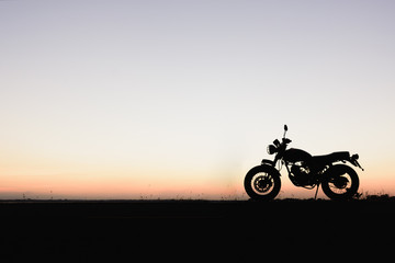 Silhouette of a motorcycle with sunset background