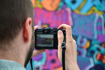 A young graffiti artist photographs his completed picture on the wall. The guy uses modern technology to capture a colorful abstract graffiti drawing. Focus on the photographing device