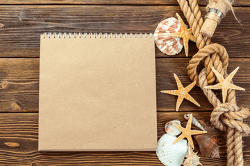 Shells and notepad on wooden table. Top view with copy space