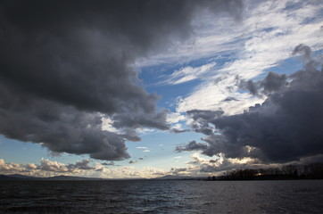 A deep and dramatic sky with big clouds over a lake