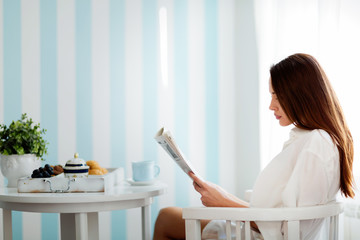 Peaceful young woman reading magazine at home