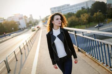 Portrait of young beautiful woman standing on bridge