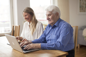 Girl with grandfather sitting by computer and tablet
