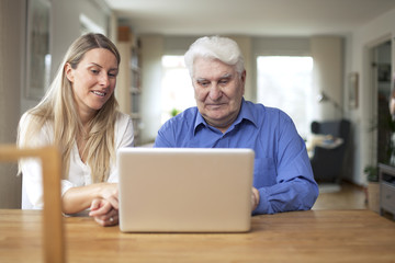 Girl showing her grandad how the computer works