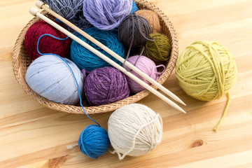 Set of colored yarn balls and needles on straw plate, wooden table as a background