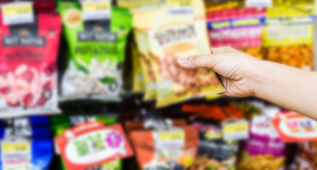 hand of woman choosing or taking sweet products, snacks on shelves in convenience store Fototapete