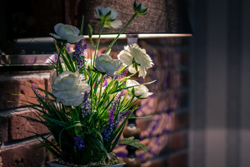 Flowers in a cafe near a brick wall