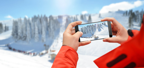 Man at the top of mountain taking photo of ski slope with phone