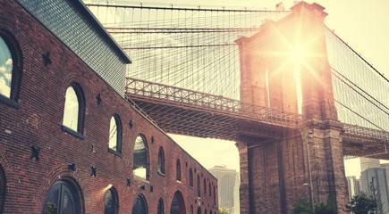 Brooklyn Bridge at sunset with lens flare, color toning applied, New York City, USA.