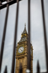 Horizontal view of the Big Ben tower seen behind bars on a dark day, UK