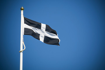 Cornwall flag flying against clear blue sky background