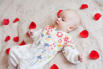 Cute baby girl lies in flower petals