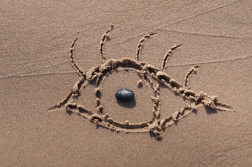 eye drawn in the sand. Beach background. Top view