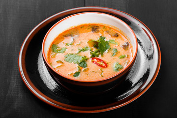 Soup with meat in bowl with oregano, peppers and vegetables on dark wooden background. Homemade food