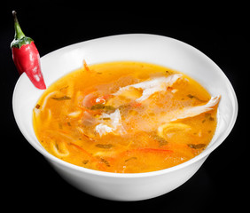 Soup chicken - broth with noodles, herbs, pepper and vegetables in bowl, isolated on black background, healthy food