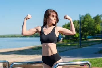 Girl in sport. Demonstration inflated muscles