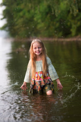 Beautiful fairy girl  with long hair standing in the river in a forest. Fairy girl mermaid in the river
