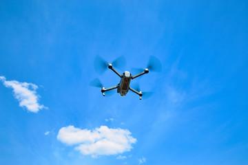 Flight of a gray quadrocopter against a blue sky.