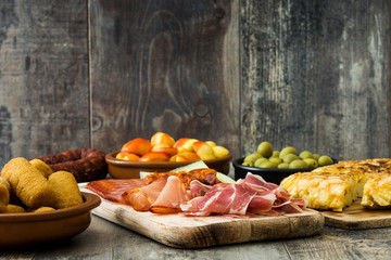 Traditional spanish tapas. Croquettes, olives, omelette, ham and patatas bravas on wooden table