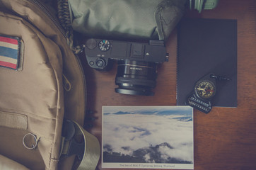 Hiking accessories set on wooden background with bag camera postcard glasses compass vintage