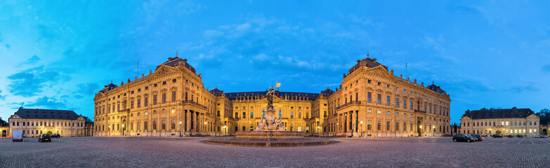 Panoramic view of illuminated Wurzburg Residence palace from Residenzplatz square in the evening,...