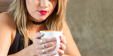 Young attractive woman drinking a delicious hot beverage