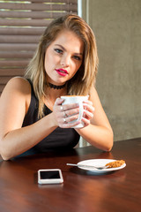 attractive woman drinking a hot beverage