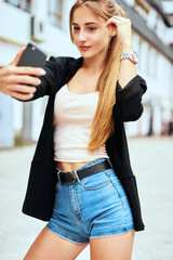 Stylish blond girl in tulle skirt and denim shirt with purple lips is having fun and makes selfie with a kiss face and with victory sign fingers with striped brown wooden balks behind.