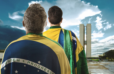 Brazilian couple holding the flag of Brazil in Brasilia