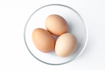 brown eggs in glass bowl on white background