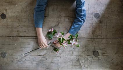 Ein Zweig mit Blüten gehalten von zwei zarten Händen auf altem Holztisch mit Patina