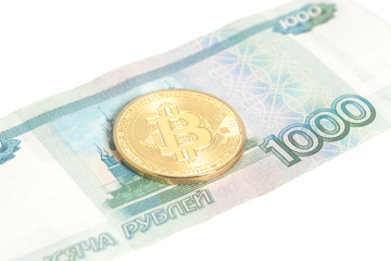 One Bitcoin on one thousand russian rubles banknotes isolated on white