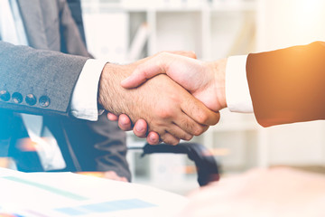 Close up of two men shaking hands in office